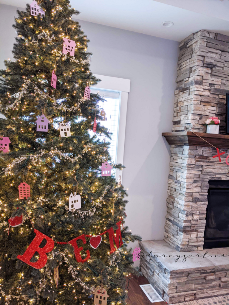 Christmas tree with pink and purple painted house ornaments and a garland that says, Be Mine.