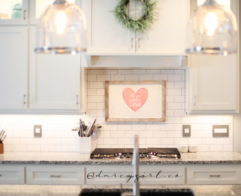 Kitchen with Valentine's Day sign, and a wreath above a stove.