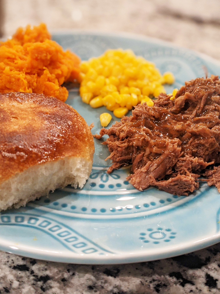 plate with beef, a roll, corn and yams.