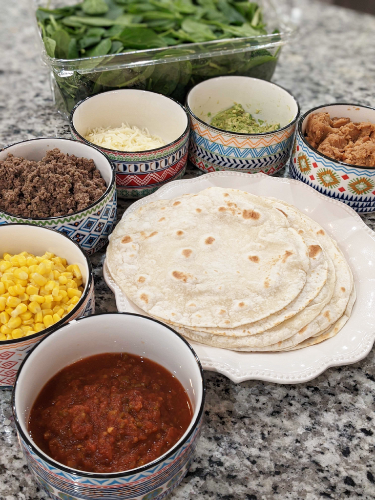Taco bar with 6 bowls with taco fixings, and tortillas in the middle.