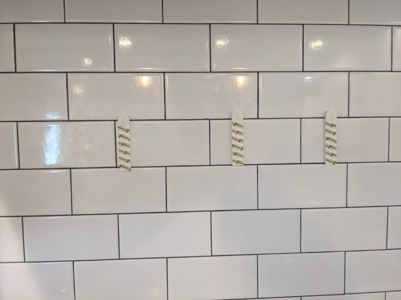Tile with command strips on it.