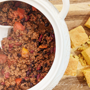 Bowl of chili with cornbread on the side,