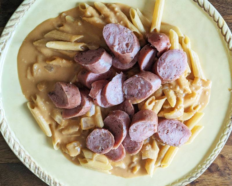 Dairy-free pumpkin alfredo sauce over penne pasta and chicken sausage on top.